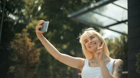 przedwiośnie : A young blond woman doing a selfie photo, smiling, expresses a different emotion, against a glass wall background.