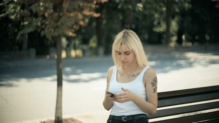 fur headphones : A young blonde woman walks in the city, sits down on the bench, reads the message in the smartphone quietly. Camera tracking Stock Footage
