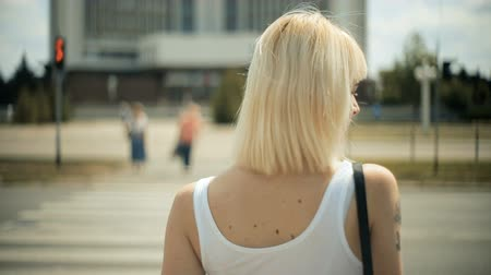 animal jovem : A young blond woman waits for cars to pass, going to cross the road, a red light, a crossing. Cars are passing by. Back view close-up