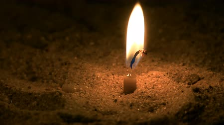 duše : A small candle burns. It is in the sand.