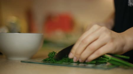 erva doce : Young woman girl slices dill on a glass board. In the kitchen.