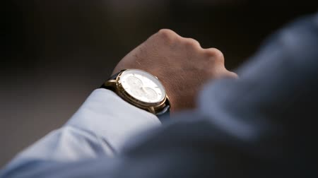 punctuality : Young male business man is waiting for a meeting. Hand with a clock close up. Waits. Looks at the clock, time. Stock Footage