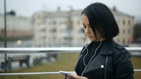 stahování : Beautiful young woman prints text in smartphone, listening to music on headphones. Brunette in the city open spaces fall. Slowmotion