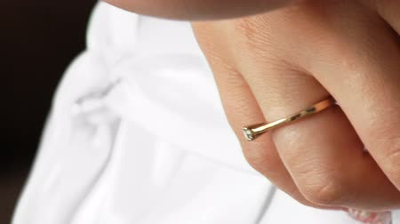 establishment : Engaged. Close-up of a hand, a gold ring with a precious stone. Wedding. White dress. Bride.