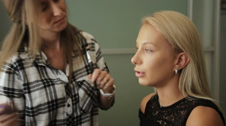 representante : Beauty saloon. A woman puts on a blonde concealer with a brush on her skin.