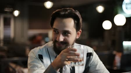 jewish : A brunette man sits alone in a bar and drinks whiskey. Smiling, happy, talking. Stock Footage