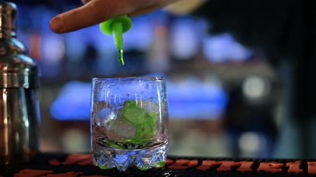 hizmet etmek : Barman mixes green apple alcoholic drink with ice and whiskey.