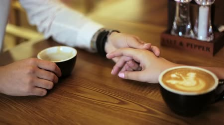 perfurante : Young couple of lovers are sitting in a cafe, drinking coffee, happy, smiling. Hands close up.
