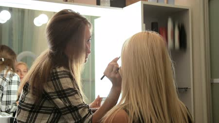 Beauty saloon. Makeup artist paints eyebrows with a brush. Blonde woman Backview