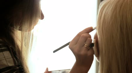 aplikatör : Beauty saloon. Makeup artist paints eyebrows with a brush. Blonde woman Close-up Backview