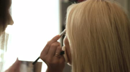 Beauty saloon. Makeup artist paints eyebrows with a brush. Blonde woman Close-up Backview