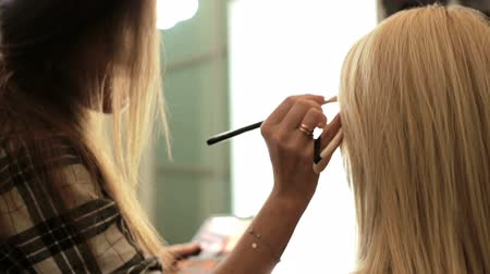 rímel : Beauty saloon. Makeup artist paints the shadows on the eyes with a brush. Blonde woman