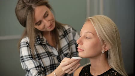 стегать : Beauty saloon. A woman applies a blonde foundation to her skin. Стоковые видеозаписи