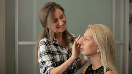 Beauty saloon. A woman applies a blonde foundation to her skin. Vídeos