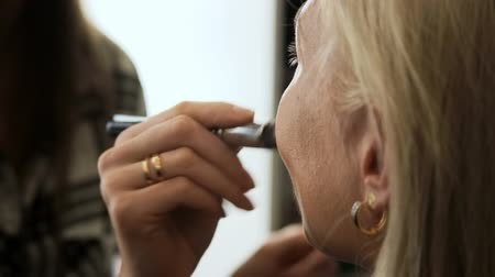 Beauty saloon. Woman gets concealer brush blonde skin.