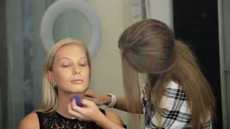 Beauty saloon. Makeup artist puts, sponge, concealer blonde on skin Reflection in the mirror
