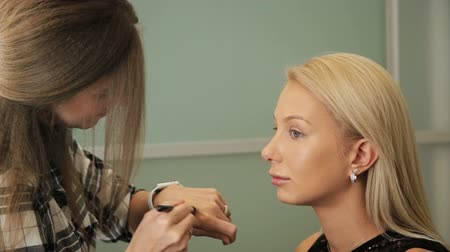 Beauty saloon. A woman puts on a blonde concealer with a brush on her skin.