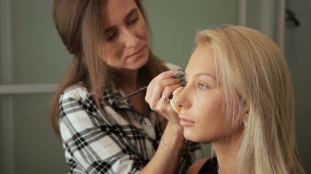 Beauty saloon. Makeup artist paints eyebrows with a brush. Blonde woman Vídeos