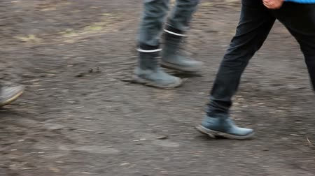 A group of working people walking on the field in cloudy weather. Boots in the mud. Slide