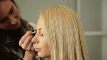 ábrázat : Beauty saloon. Makeup artist paints the shadows on the eyes with a brush. Blonde woman