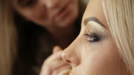 Beauty saloon. Makeup artist paints the shadows on the eyes with a brush. Blonde woman Close-up