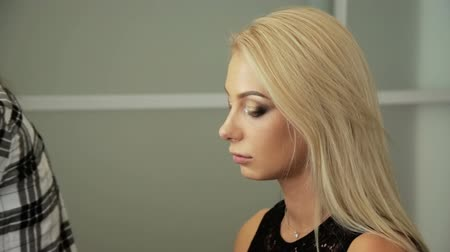 vurgulayıcı : Beauty saloon. Makeup artist paints the shadows on the eyes with a brush. Blonde woman