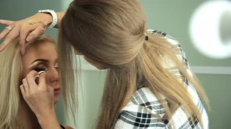 Beauty saloon. Makeup artist paints the shadows on the eyes with a brush. Blonde woman Reflection in the mirror Stock mozgókép