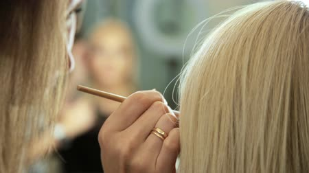 Beauty saloon. Makeup artist paints the shadows on the eyes with a brush. Blonde woman Close-up Reflection in the mirror