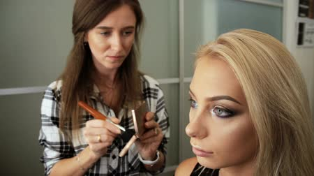 Beauty saloon. Makeup artist paints the shadows on the eyes with a brush. Blonde woman