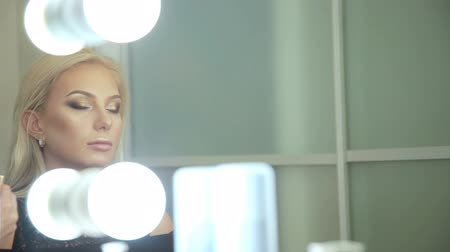 eyeshade : Beauty saloon. Makeup artist paints the shadows on the eyes with a brush. Blonde woman Reflection in the mirror Stock Footage