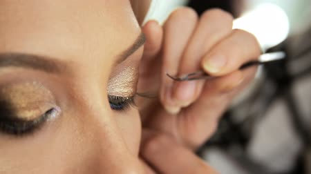 barok : Beauty saloon. Makeup artist sticks eyelashes to blonde eyes Close-up Stok Video
