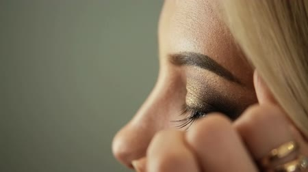 frizura : Beauty saloon. Makeup artist sticks eyelashes to blonde eyes Close-up Stock mozgókép