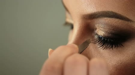 ヘッドドレス : Beauty saloon. Makeup artist sticks eyelashes to blonde eyes Close-up 動画素材