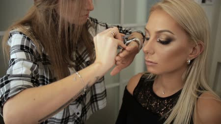 Beauty saloon. Makeup artist sticks eyelashes to blonde eyes