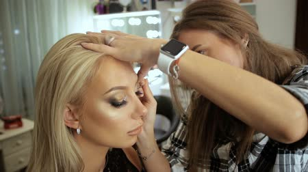 aplikatör : Beauty saloon. Makeup artist draws arrows, eyeliner, blonde Eye pencil