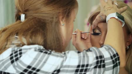 Beauty saloon. Makeup artist draws arrows, eyeliner, blonde Eye pencil