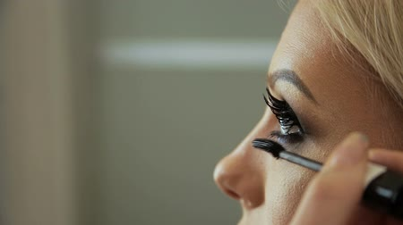 стегать : Beauty saloon. Makeup artist induces eyelashes with a brush-mascara, blonde. Eye pencil.