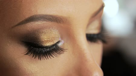 Beauty saloon. Makeup artist induces eyelashes with a brush-mascara, blonde. Eye pencil.