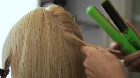 Beauty saloon. Hairdresser styling hair in a blonde hairstyle.