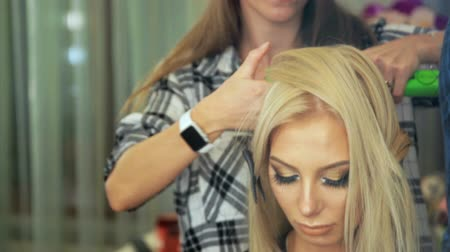 grzebień : Beauty saloon. Hairdresser styling hair in a blonde hairstyle.