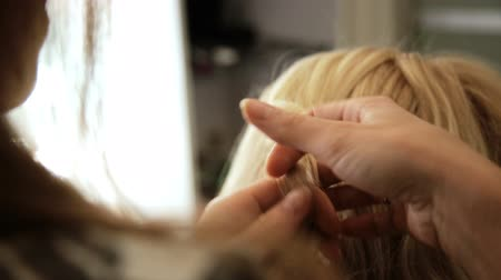 warkocz : Beauty saloon. Hairdresser styling hair in a blonde hairstyle.