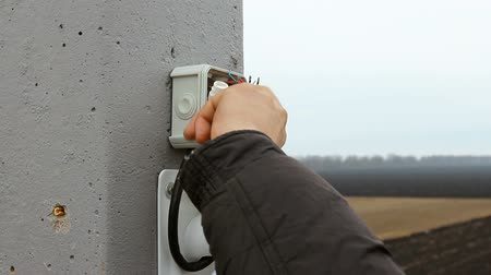 guards : An electrician man repairs installs a video surveillance system. Stock Footage