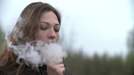 kötü : Young woman smoking a hookah outdoor Stok Video