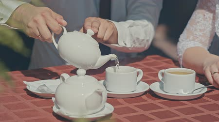 tarde : tea from a teapot poured into the Cup, hands Vídeos