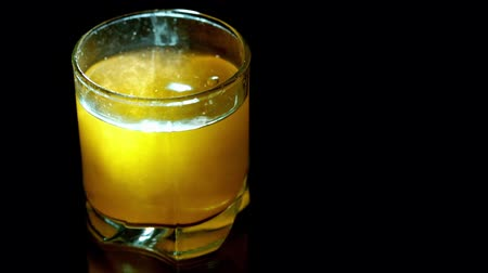 barmetro : yellow cocktail in glass on black background Stock Footage