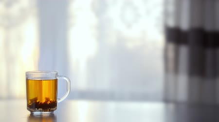 demlik : a Cup of steaming hot tea on the table against the window