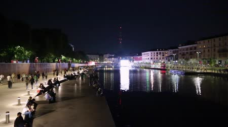 yeniden yapılanma : Milan new Darsena, redeveloped docks area at night, people walking and chatting on May 30, 2015 in Milan Italy. The Darsena, the canal port closed since 1979 was reopened in April 2015. Stok Video