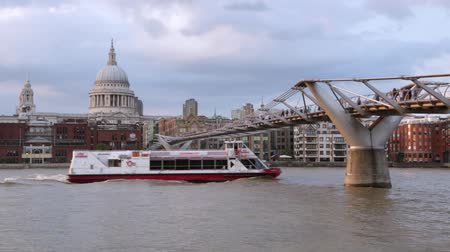 Millennium bridge with people walking and St Paul cathedral in a summer evening, boat passing on August 7, 2015 in London. The footbridge crosses the river Thames linking Bankside with the City of London.