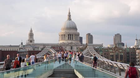 Millennium bridge with people walking and St Paul cathedral in a summer evening on August 7, 2015 in London. The footbridge crosses the river Thames linking Bankside with the City of London.
