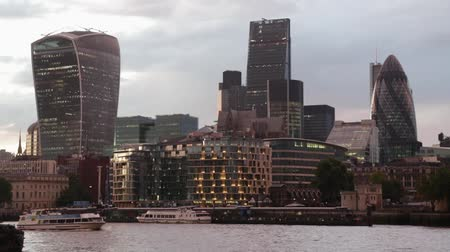 London skyscrapers skyline view at sunset, boat passing with Thames river in the evening on August 5, 2015 in London.